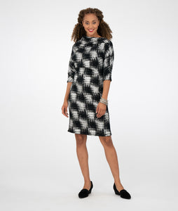 model in a black and silver checkered print shift dress with an asymmetrical neckline