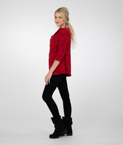 model in black leggings with a red top with an asymmetrical neckline, in front of a white background