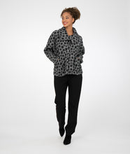 Load image into Gallery viewer, model in a short grey jacket with black square print, worn with black leggings in front of a white background