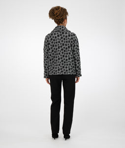 model in a short grey jacket with black square print, worn with black leggings in front of a white background