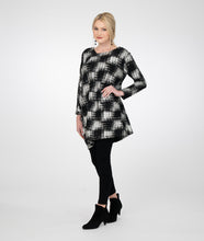 Load image into Gallery viewer, model in black leggings with a black and silver checkered style top with one asymmetrical side and sleeve