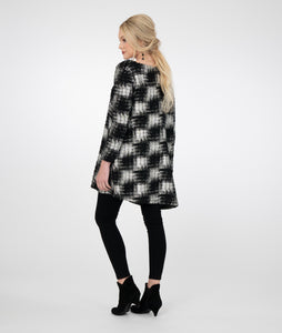 model in black leggings with a black and silver checkered style top with one asymmetrical side and sleeve
