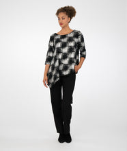 Load image into Gallery viewer, model in black pants with a black and silver checkered print top with sequins sewn sparingly throughout and an asymmetrical hemline, standing in front of a white background
