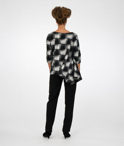 model in black pants with a black and silver checkered print top with sequins sewn sparingly throughout and an asymmetrical hemline, standing in front of a white background