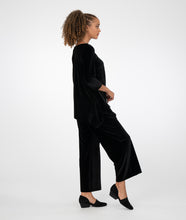 Load image into Gallery viewer, model in a black asymmetrical top with a wide leg pant, in front of a white background