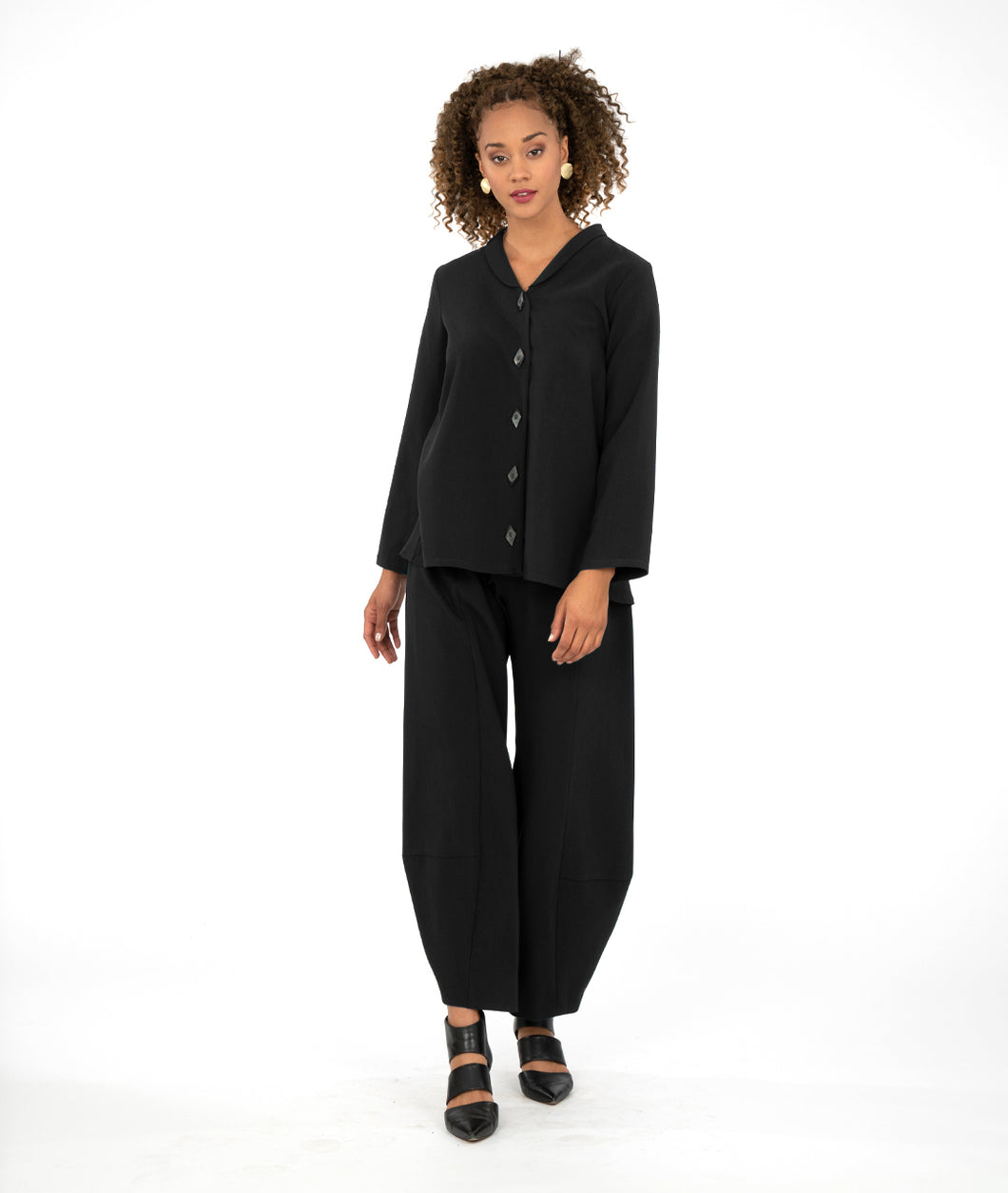 model in a black button up blouse with a wide leg black pant that tapers at the ankle