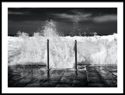 Vossington wall art and fine art photography of an ocean scenery with stormy waves crashing against a stone pier with a ladder leading down into the sea