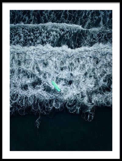 Vossington wall art and fine art photography from an aerial point of view with a surfing board floating on the waves that are crashing against an empty black beach
