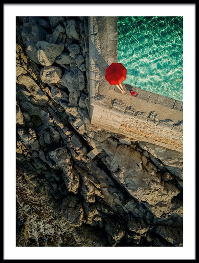 Vossington wall art and fine art photography from an aerial point of view of a woman with a red umbrella sitting by a pool in the summer