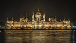 Fine photographic and art print of the Hungarian Parliament building in Budapest at nighttime with the light reflecting on the Danube River.