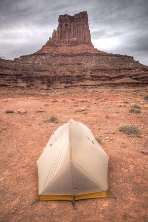 Fine photographic and art print of a small backpacker's tent in front of a red stone monument along Canyonlands National Park's White Rim Trail in Utah.