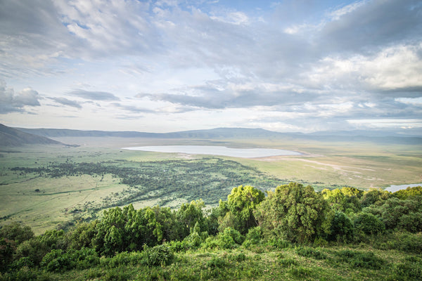 Fine Ngorongoro Crater photography print of the expansive crater atop the rim as the clouds breach the crater, casting shadows on the luscious landscape.