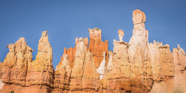 Fine Bryce Canyon National Park photography print of an array of orange and white hoodoo rock features against a blue sky backdrop.