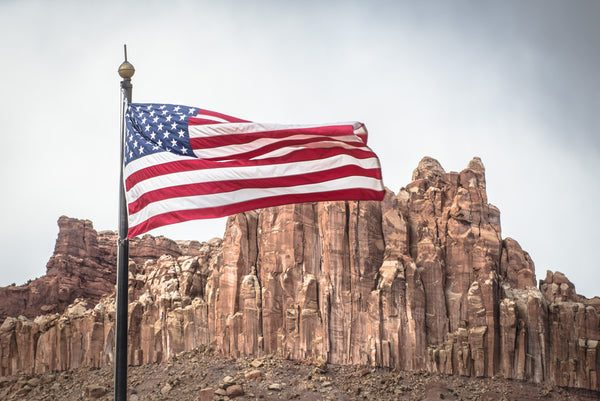 Fine Capitol Reef National Park photography print of an American flag blowing in the wind with rock formations in the background.