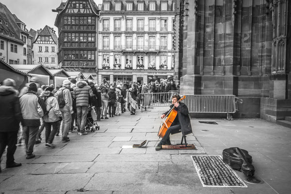 Fine black and white photographic and art print of a solo colorful cellist playing outside the doors of Strasbourg Cathedral as Christmas crowds gather and listen as they wait to enter.