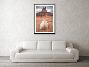 Framed fine photographic and wall art print of a small backpacker's tent in front of a red stone monument along Canyonlands National Park's White Rim Trail in Utah.