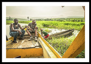 Framed fine photographic and art print of three Congolese men operating a wooden boat and small wooden canoe along the Congo River during the day in the Democratic Republic of the Congo.