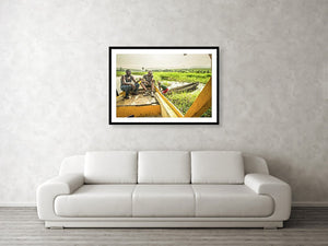 Framed fine photographic and wall art print of three Congolese men operating a wooden boat and small wooden canoe along the Congo River during the day in the Democratic Republic of the Congo.