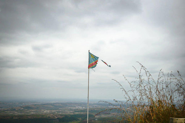 Fine photographic and art print of a ripped Democratic Republic of the Congo flag on top of a mountain overlooking a small village.