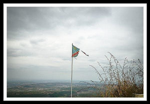 Framed fine photographic and art print of a ripped Democratic Republic of the Congo flag on top of a mountain overlooking a small village.