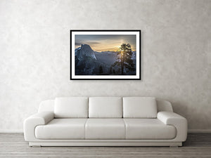 Framed fine photographic and wall art print of sunrise at Glacier Point in Yosemite National Park in California with Half Dome in the near distance and a tree in the foreground.