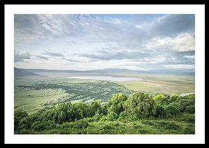 Framed fine Ngorongoro Crater photography print of the expansive crater atop the rim as the clouds breach the crater, casting shadows on the luscious landscape.