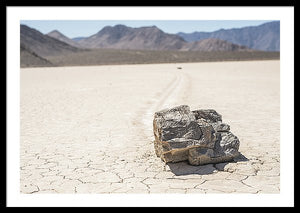 Framed fine photographic and art print of a single jagged rock carving a mysterious path through a cracked desert floor in Death Valley National Park in California.