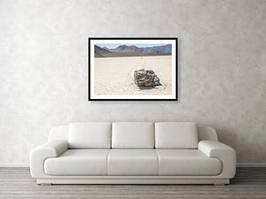 Framed fine photographic and wall art print of a single jagged rock carving a mysterious path through a cracked desert floor in Death Valley National Park in California.