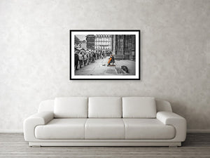 Framed fine black and white photographic and wall art print of a solo colorful cellist playing outside the doors of Strasbourg Cathedral as Christmas crowds gather and listen as they wait to enter.