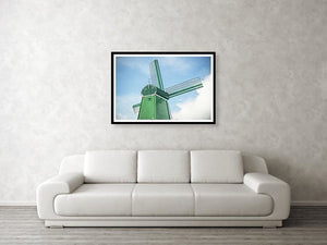 Framed fine photographic and wall art print of a single green windmill against a backdrop of blue dutch skies.