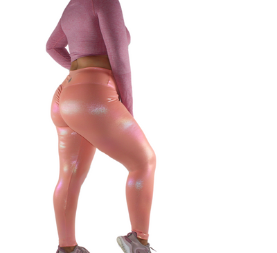 Fairy dust collection legging in Peach Rosé. Made to stand out and shine, our all over iridescent print shimmers like the eyes of someone in love. High waisted to snatch you in where you need it, but also buttery soft enough to wear all day and night long. This Legging is high waisted for ultimate comfort and compression. The backside features a slight scrunch to accentuate your bum. scrunch butt, full length, shiny, high waisted. elle athletix