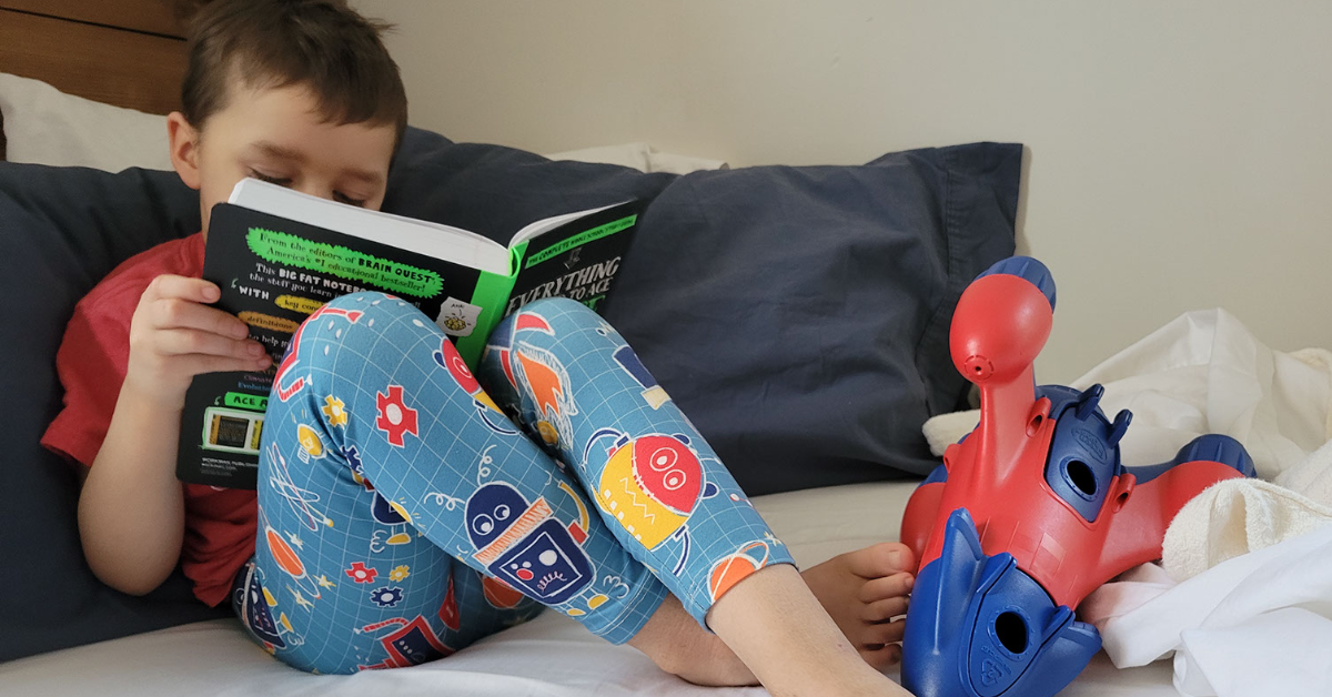 child reading a book with robot leggings and spaceship toy