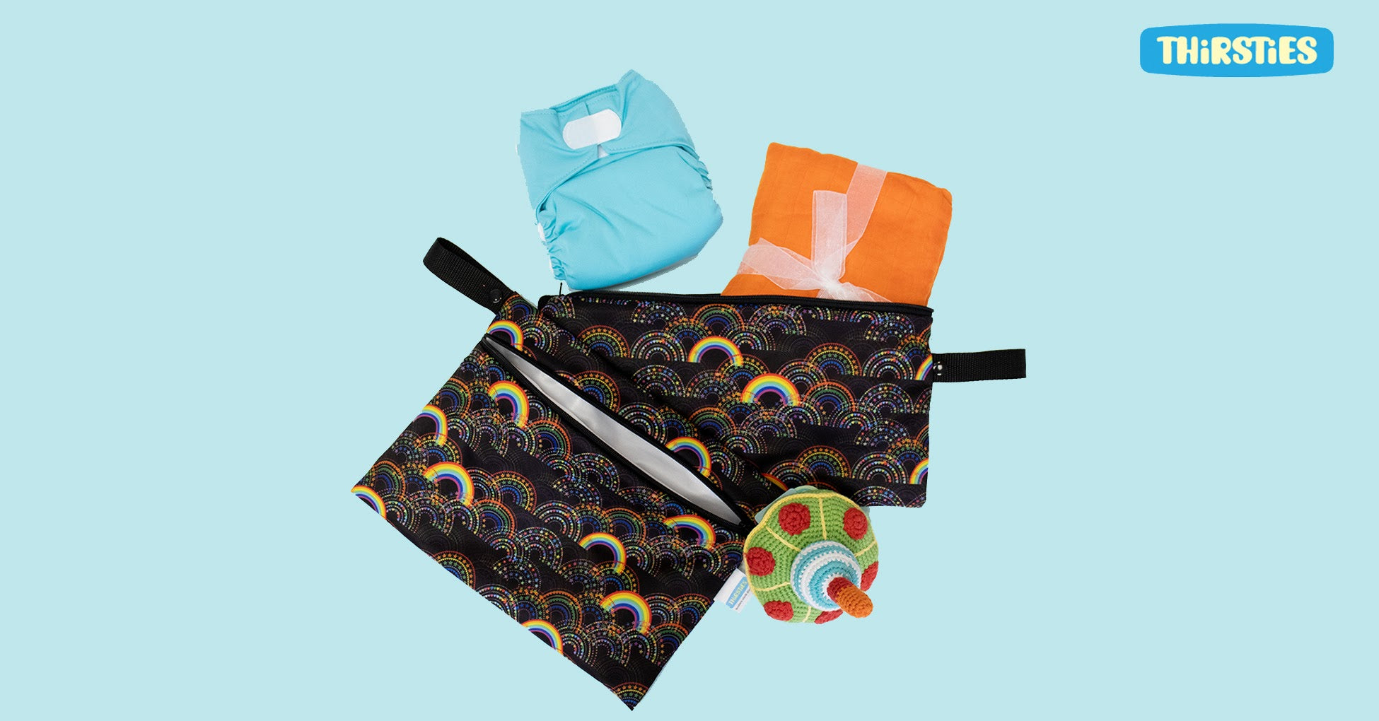 two thirsties wet bags with cloth diapers and swaddle blanket