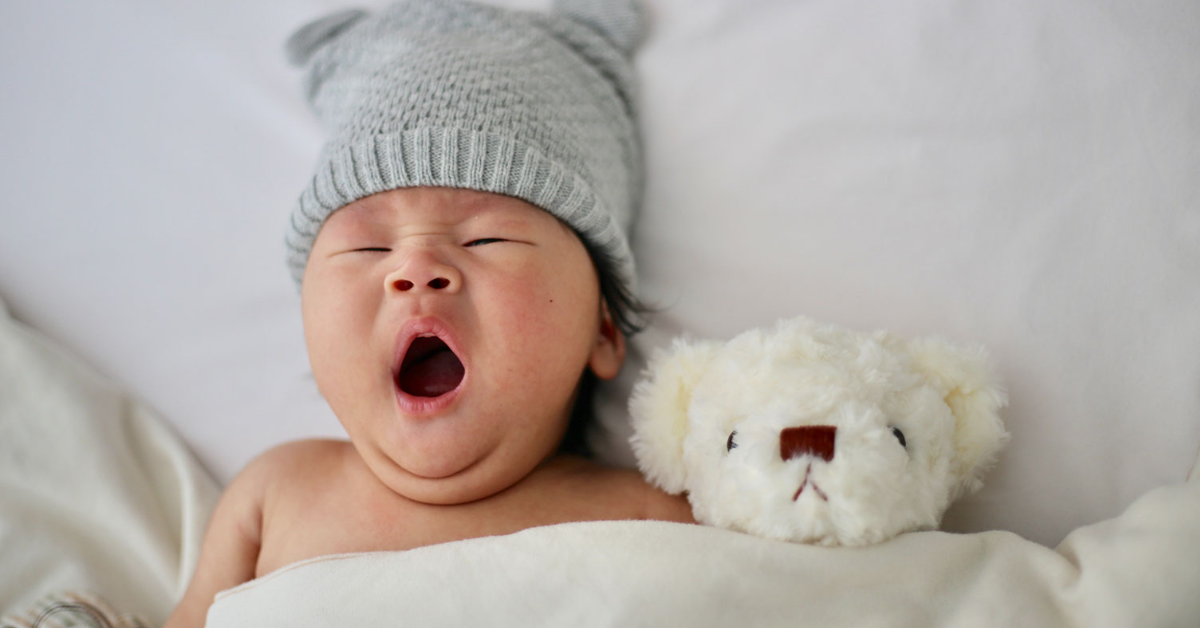 baby in hat yawning