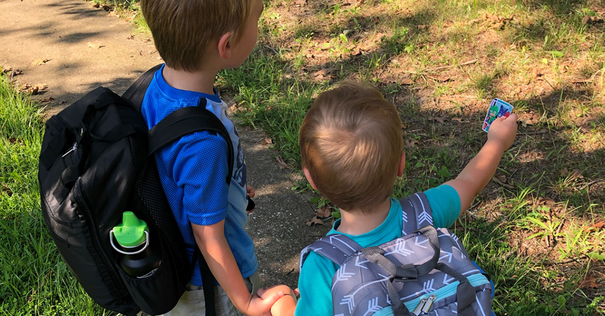 Two boys with backpacks outside