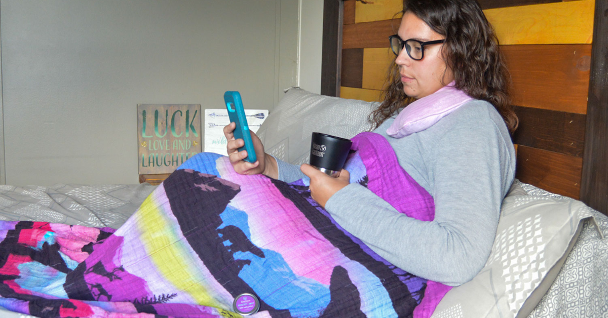 Woman with book, coffee, and blanket