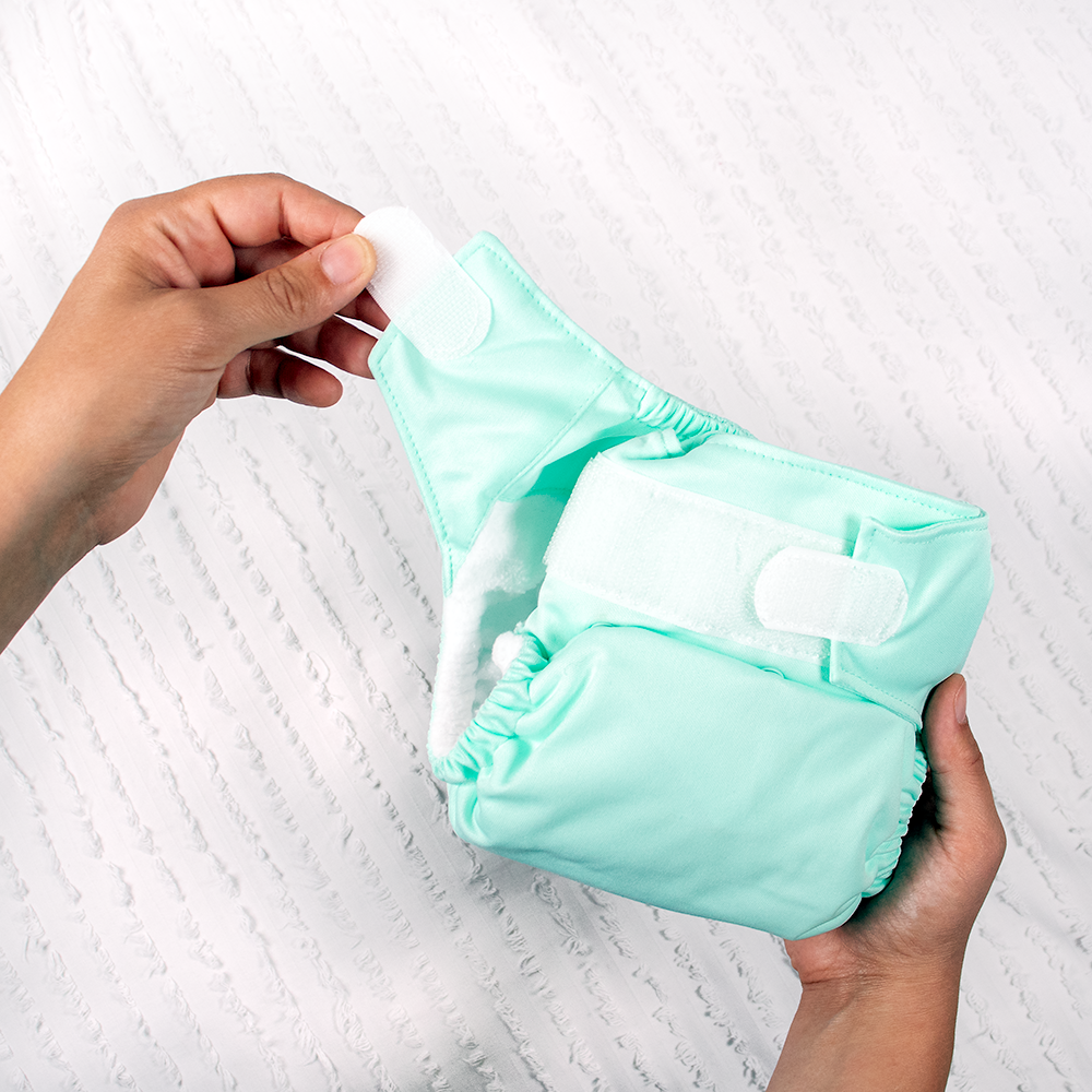 Person holding Nicki's Ultimate All in One Hook and Loop Diaper emphasizing the hook and loop feature