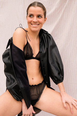 A woman wearing a black bralette made with plumeti fabric.
