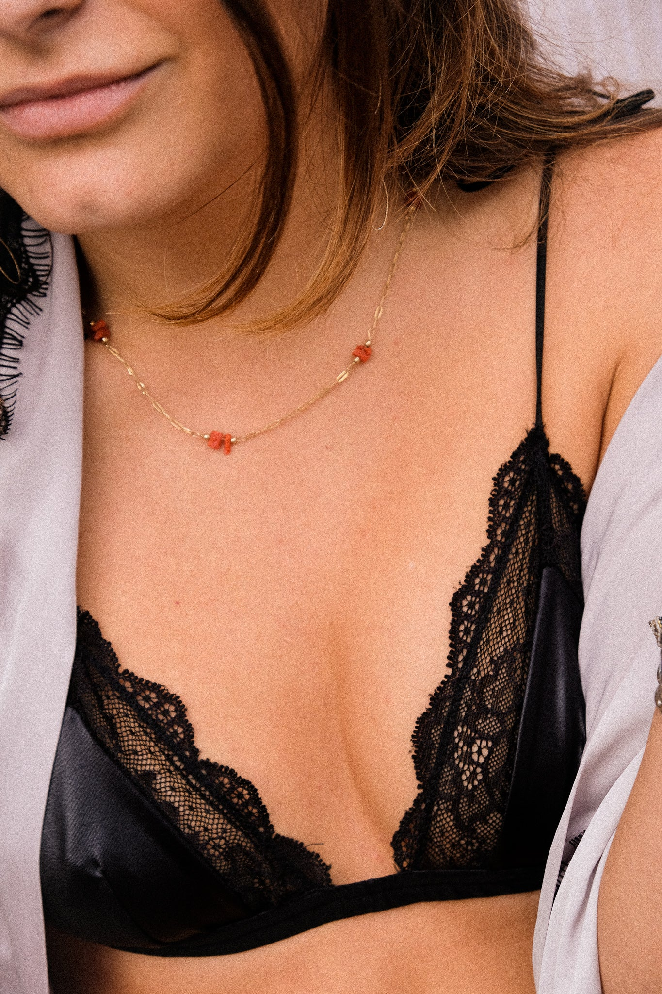 A woman wearing a satin black bralette.