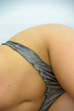 Load image into Gallery viewer, A woman wearing a gold brief made with satin fabric.