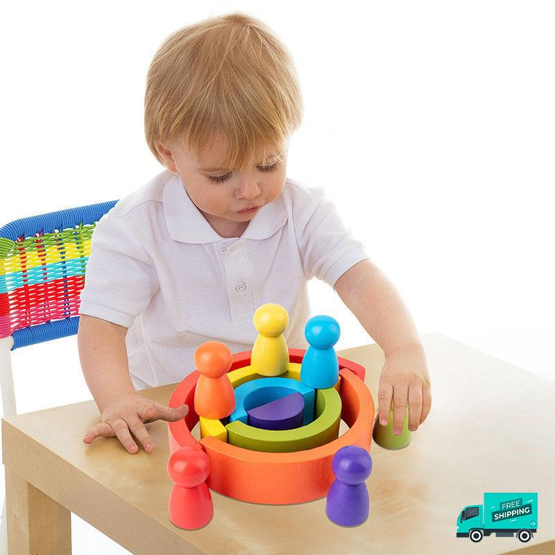 Kid playing Wooden Rainbow Blocks in the table