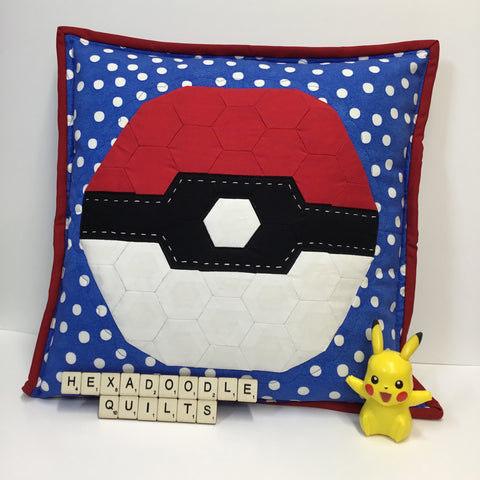 Picture showing Monster Ball EPP pattern made into a cushion with plastic Pikachu toy sitting next to it