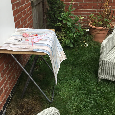 Picture showing folding table set up in a garden against a brick wall with Sewing Hexessories samples laid out on top
