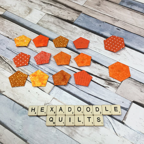 hexagon and pentagon paper shapes basted with a variety of orange fabrics
