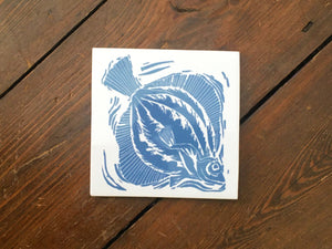 Plaice handmade tile trivet lino cut by Kate Guy in dark blue