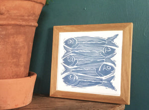Sardines tile trivets in oak frames lino cut by Kate Guy
