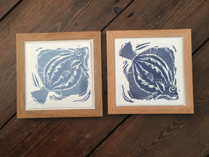 Plaice tile trivets in oak frames lino cut by Kate Guy in dark and pale blue