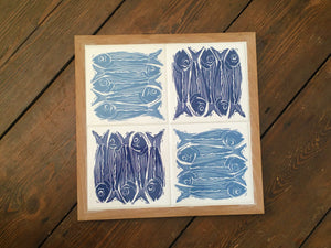 Sardines tile trivet table centrepiece in oak frames lino cut by Kate Guy in dark and pale blue