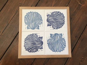 Scallop Shell Handmade tile trivet, table centrepiece. Linocut print of scallop shells in pale and dark blue on four tiles framed in English oak