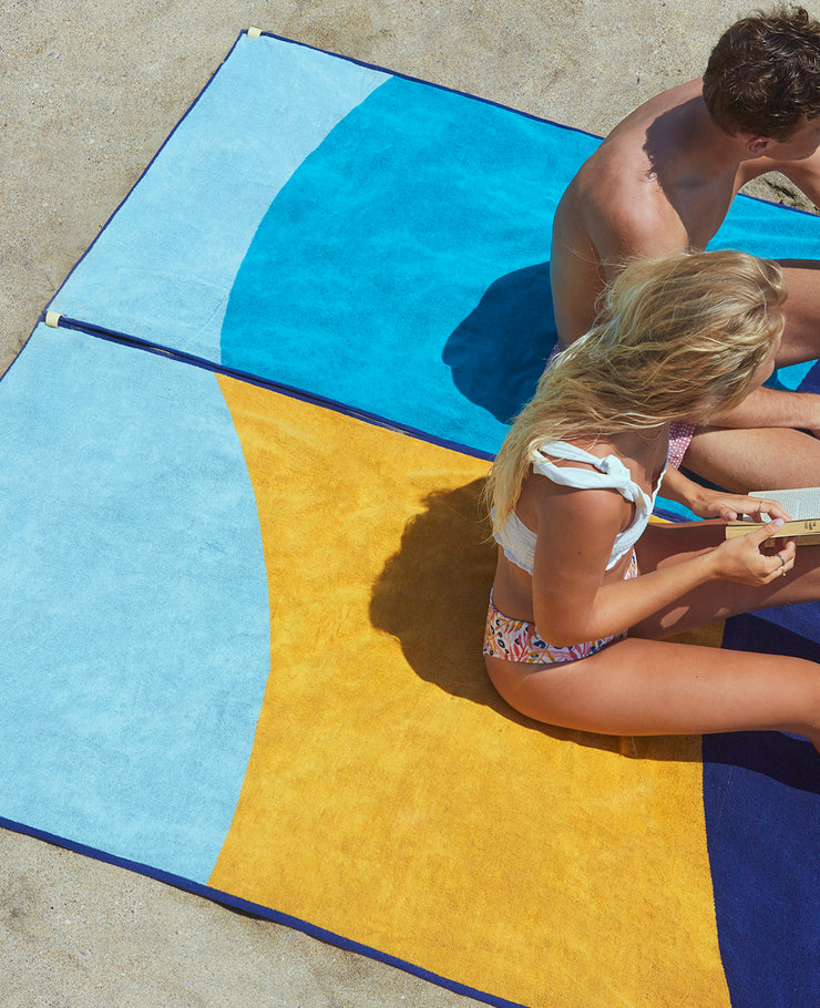 A couple over two Tucca beach towels connected, linking designs with no sand in between.